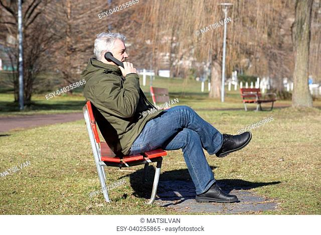Man sitting on a bench and speaking on the telephone