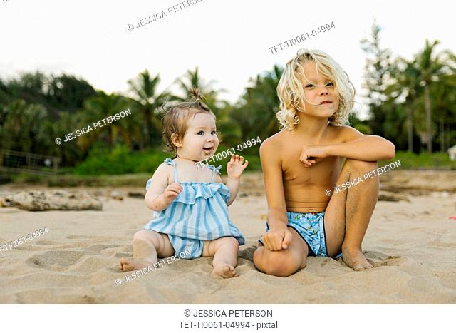 Boy and his baby sister sitting on beach