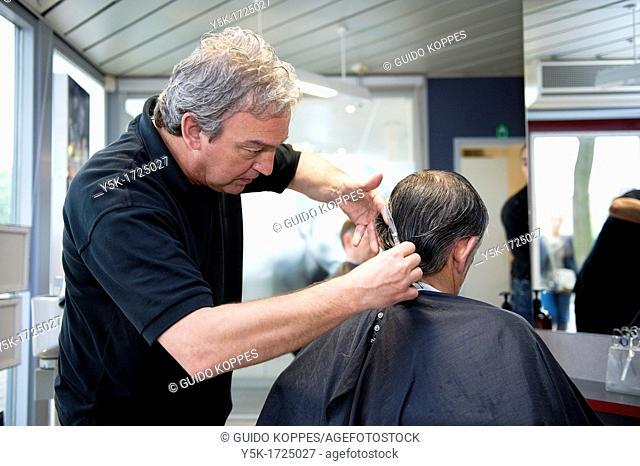 A barber giving a male customer a haircut