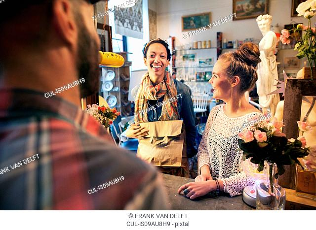 Two happy young female customers buying from vintage shop
