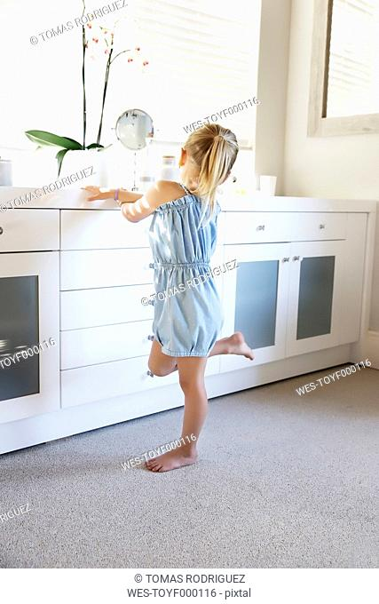 Little girl standing in bright bathroom