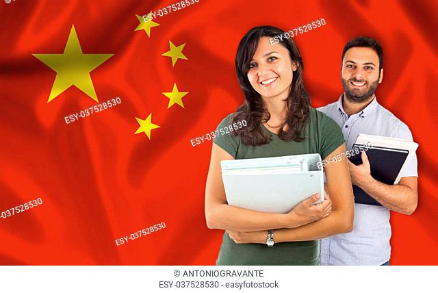 Couple of young students with books over chinese flag
