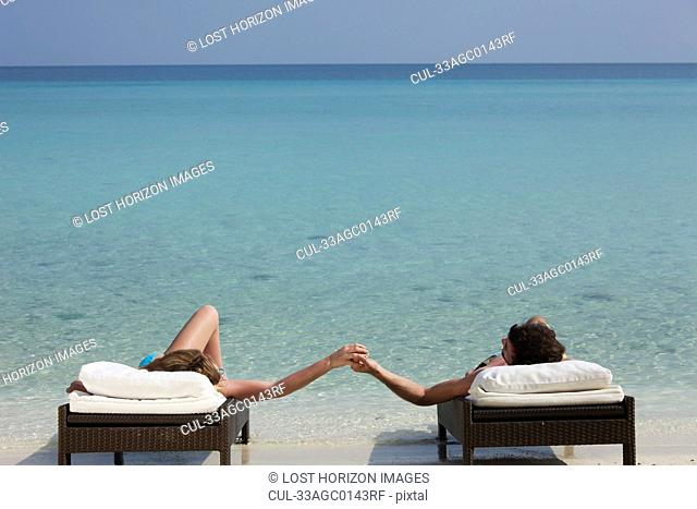 Couple relaxing on daybeds at beach