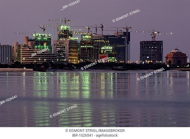 Construction site and Abu Dhabi skyline at dusk, Emirate of Abu Dhabi, United Arab Emirates, Arabia, Middle East