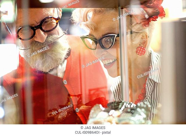 Quirky vintage couple looking at glass display case in antique emporium