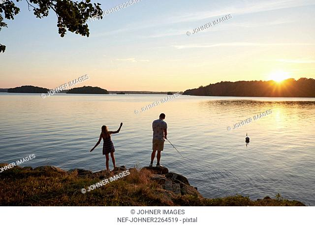 Young people fishing by lake