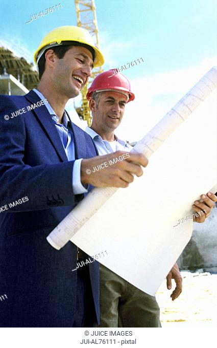 Construction worker and businessman looking at plans and smiling