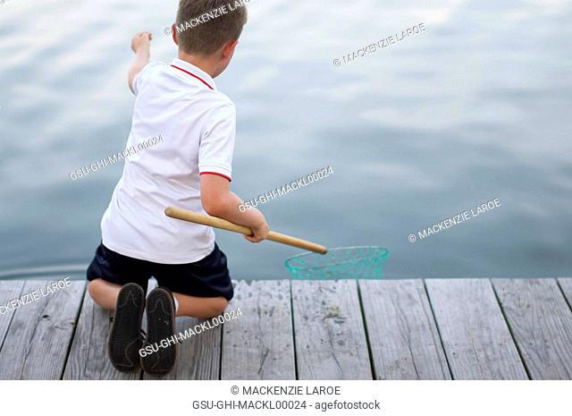 Young Boy Fishing on Dock with Net and String, Rear View