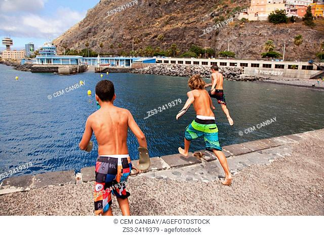 Boys jumping from the pier into the sea near the water sport club inside the harbor of Santa Cruz, Tenerife, Canary Islands, Spain, Europe