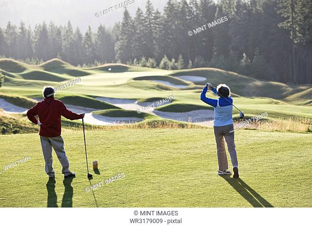 Senior woman golfer tees off with her male partner observing off to the side