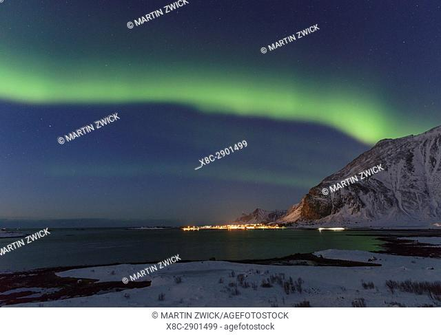 Northern Lights over Flakstadoya and village Ramberg. The Lofoten Islands in northern Norway during winter. Europe, Scandinavia, Norway, February