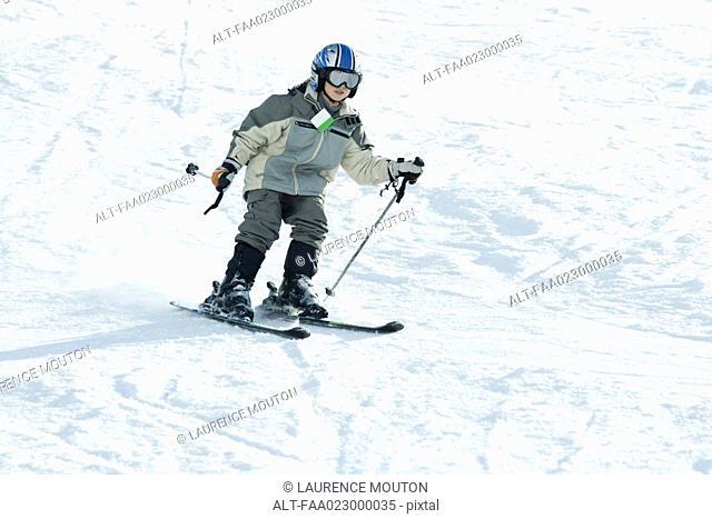 Boy skiing down ski slope, full length
