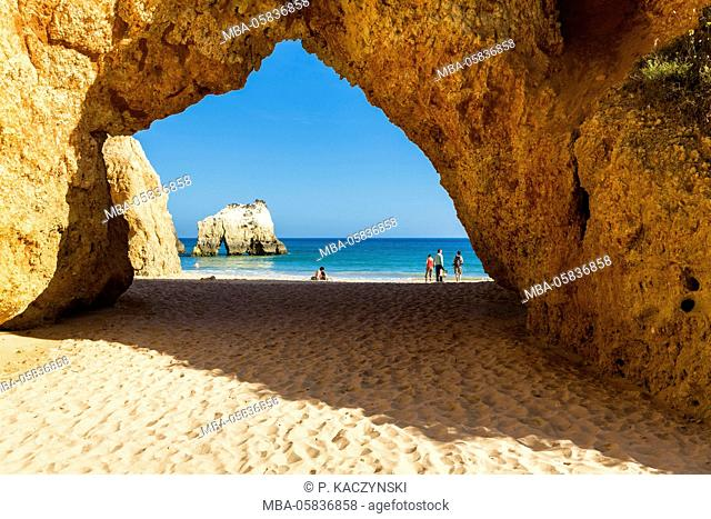 View through a little arch on the sandy beach and rocks at Praia dos Tres Irmaos, Portimao, Algarve, Portugal