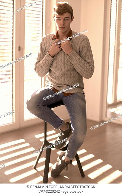 Young handsome man sitting on chair indoors next to window, student, business man