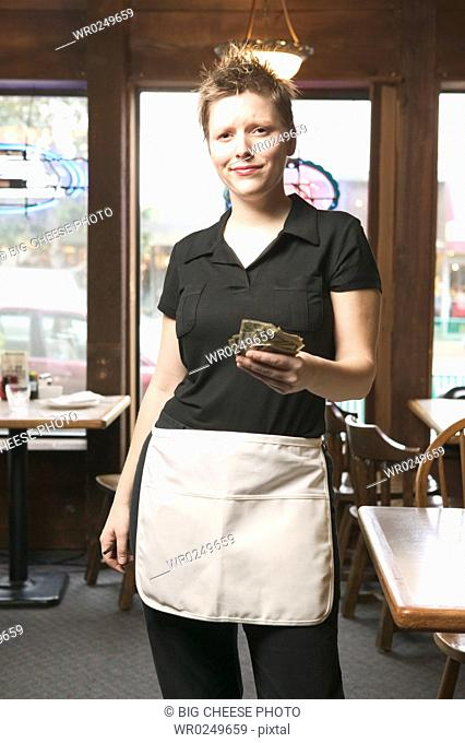 Young waitress holding out money