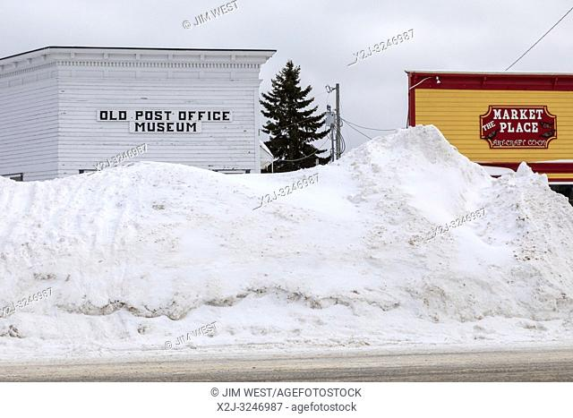 Grand Marais, Michigan - Snow is piled high in front of buildings on the main street. The town, on the shore of Lake Superior