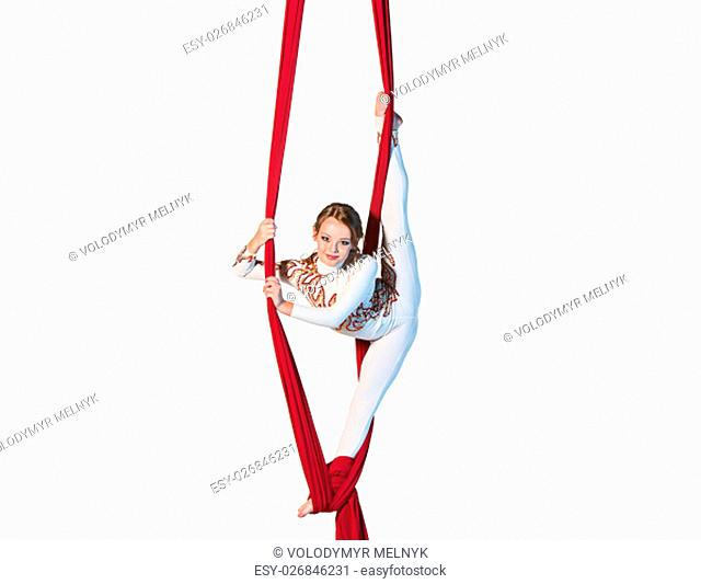 Graceful gymnast performing aerial exercise with red fabrics on white background