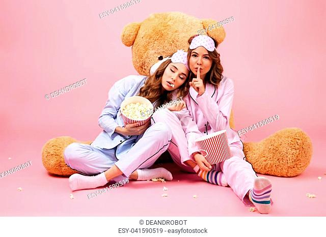 Two young pretty girls dressed in pajamas showing silence gesture while  sitting with a big teddy 776c25577