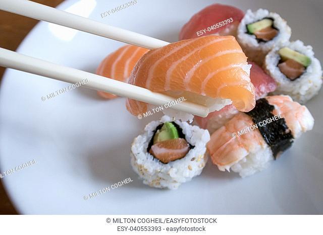 Fresh salmon nigiri sushi between chopsticks with uramaki, prawn nigiri and tuna nigiri in the background