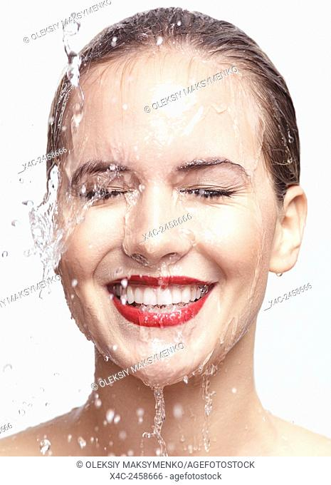 Artistic beauty portrait of a young smiling woman with water dripping over her face. Isolated on white background
