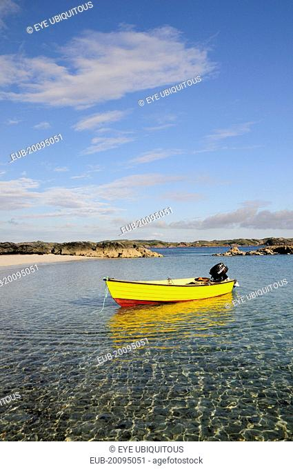 Yellow boat anchored in clear waters