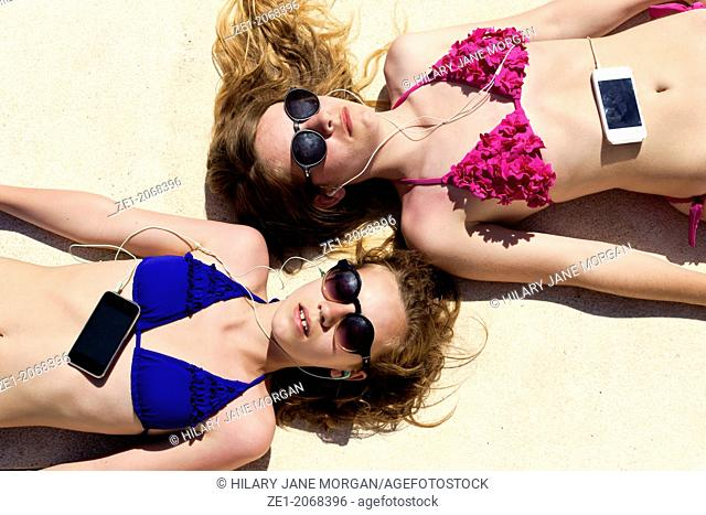 Two teenage girls lying in the sun listening to music on their mobile phones