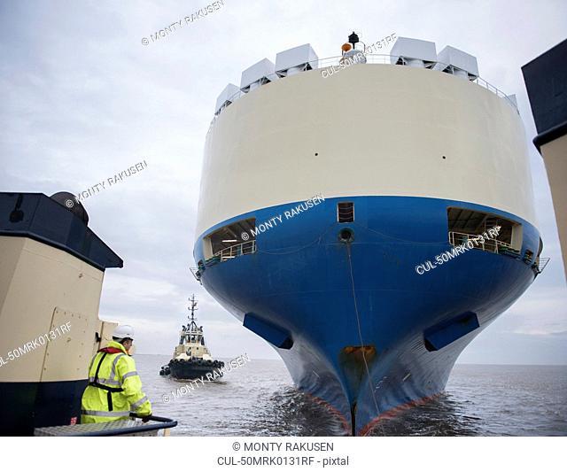 Tugboat sailing by large ship