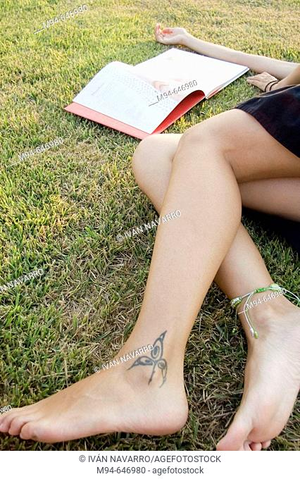 Woman laying on grass reading a book