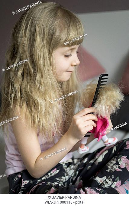 Little girl hairdressing her doll