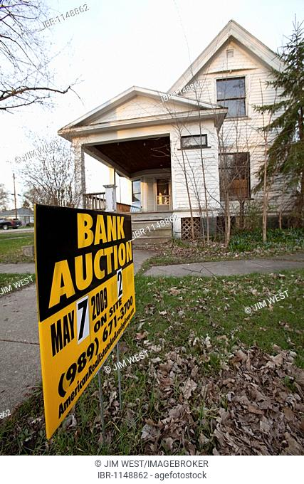 A sign advertises the upcoming bank auction of a foreclosed home in rural Michigan, Merrill, Michigan, USA