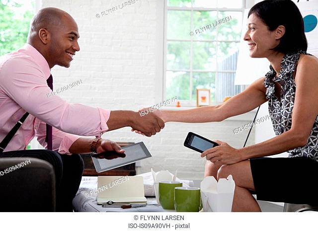 Office colleagues shaking hands in meeting, smiling