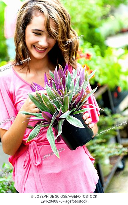 A smiling 14 year old brunette looking at a plant in plant nursery