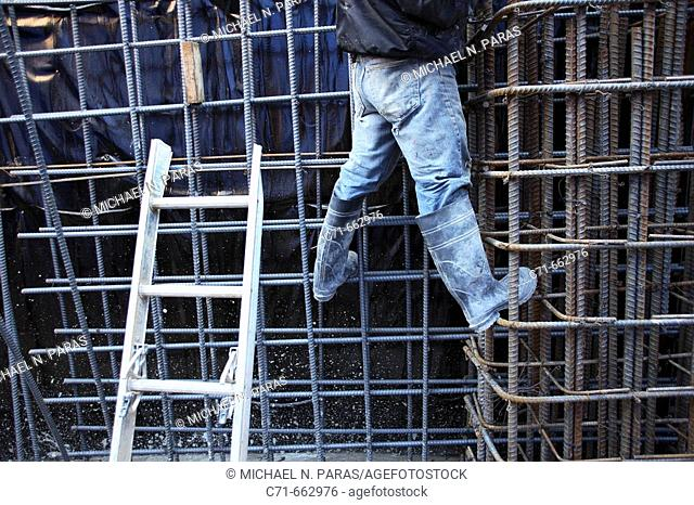 Construction worker standing on wall of steel rebar