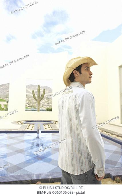 Man in cowboy hat standing next to a hotel pool, Los Cabos, Mexico