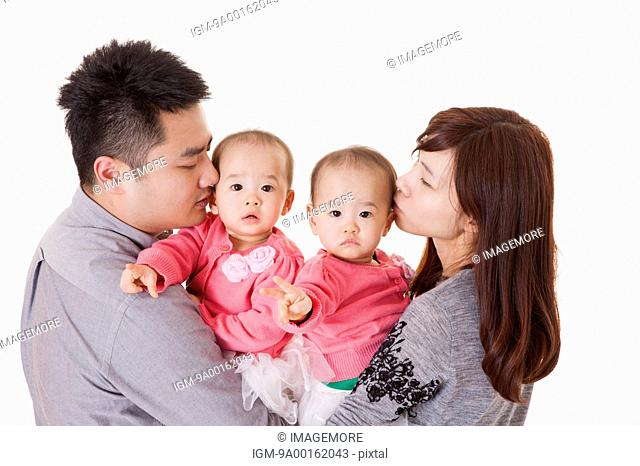 Young parents kissing baby twins and looking away