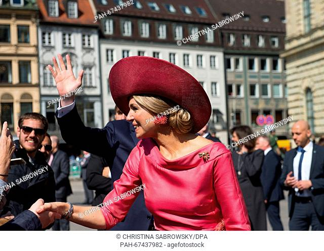 Queen Maxima (front) of the Netherlands and King Willem-Alexander (back, covered) arrive for a welcome ceremony at the Max-Joseph-Platz square during a visit of...