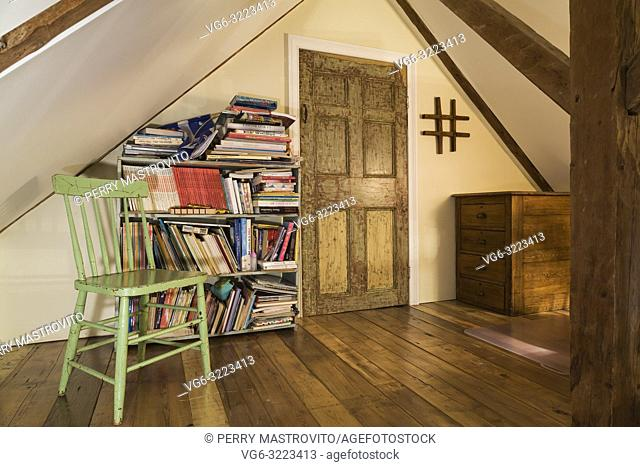 Attic room with green wooden sitting chair next to antique bookcase and stressed finish closet door inside an old 1835 fieldstone house