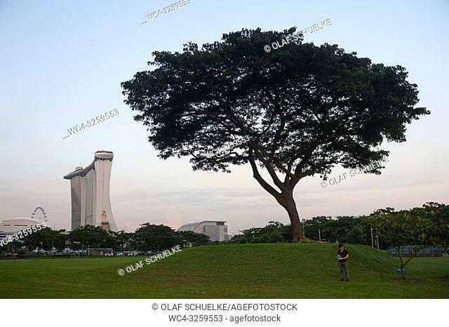 Singapore, Republic of Singapore, Asia - A man is seen standing next to a tree flying a drone over Marina Bay with the Marina Bay Sands Hotel in the backdrop