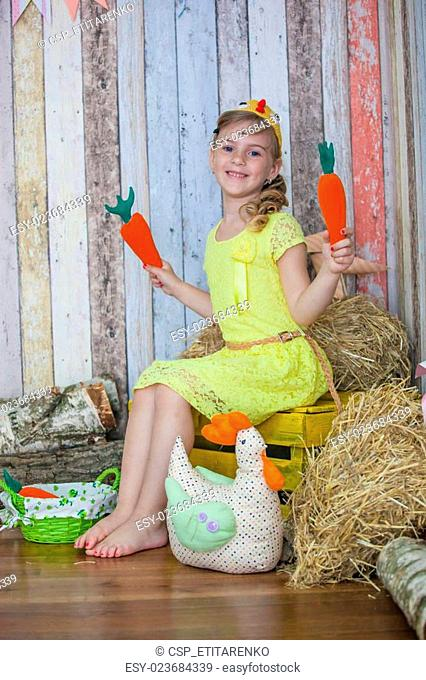 beautiful girl in the yellow dress, playing with carrot