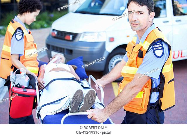 Paramedics wheeling patient on stretcher in hospital parking lot