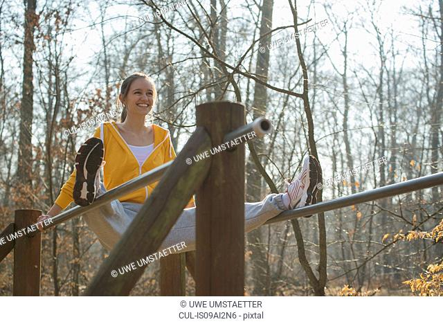 Young woman balancing on parallel bars on forest assault course