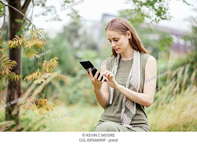 Young woman using digital tablet in field
