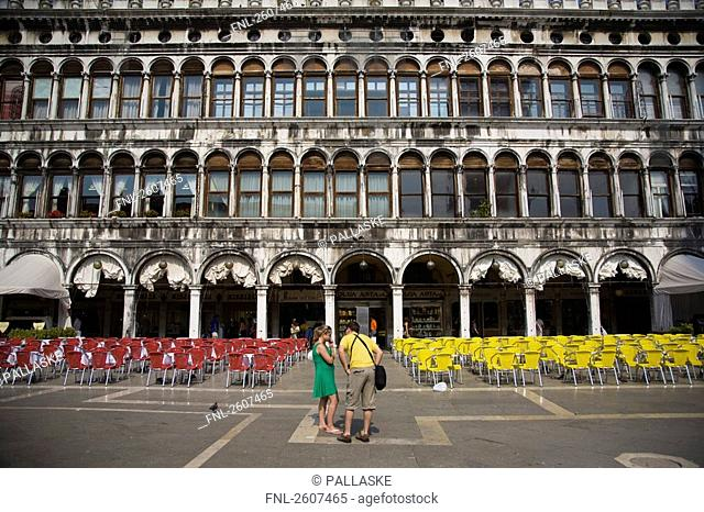 Two tourists near chairs arranged in town square, Piazza San Marco, St. Mark's Square, Veneto, Venice, Italy