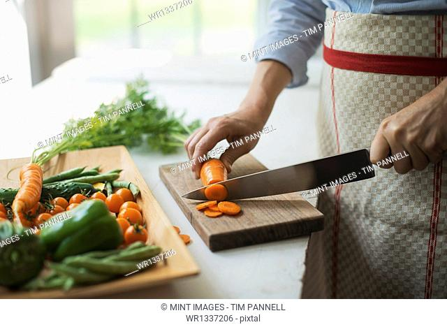 A woman preparing fresh vegetables. Slicing a carrot