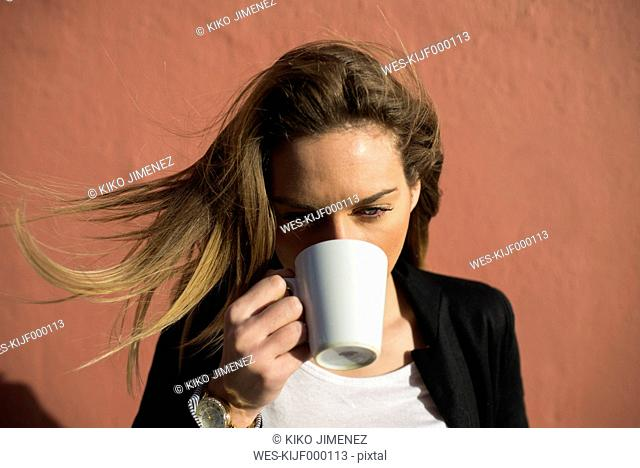 Woman with blowing hair drinking coffee