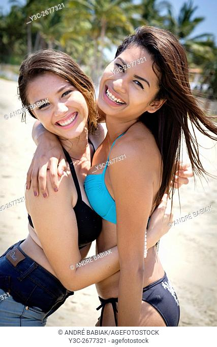 Two attractive female teenagers hugging at a beach at Riviera Nayarit, Mexico