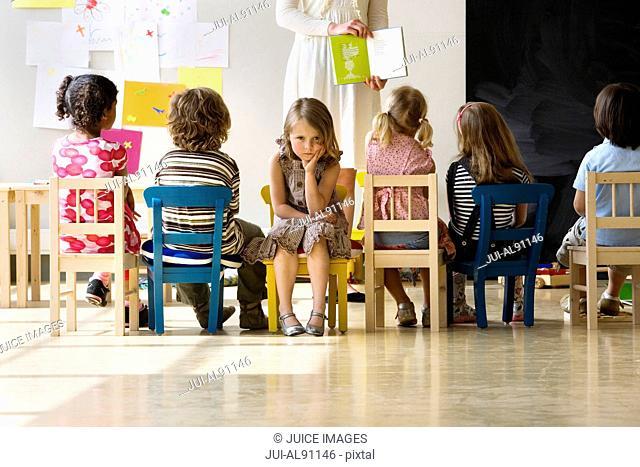 Angry girl ignoring preschool teacher reading