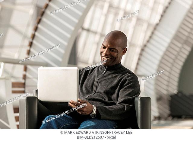 African American man using laptop in lobby