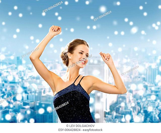 people, party, holidays and christmas concept - smiling woman dancing with raised hands over snowy city background