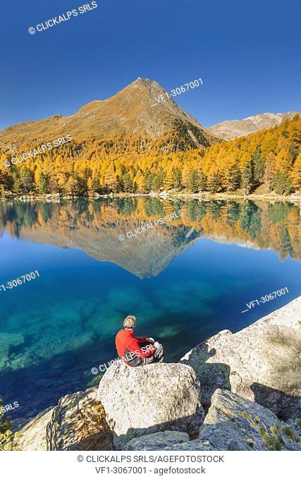 Hiker take a break to admire lake Saoseo in a perfect autumn day, Poschiavo, val di Campo, Canton of Graubunden, Switzerland, Europe